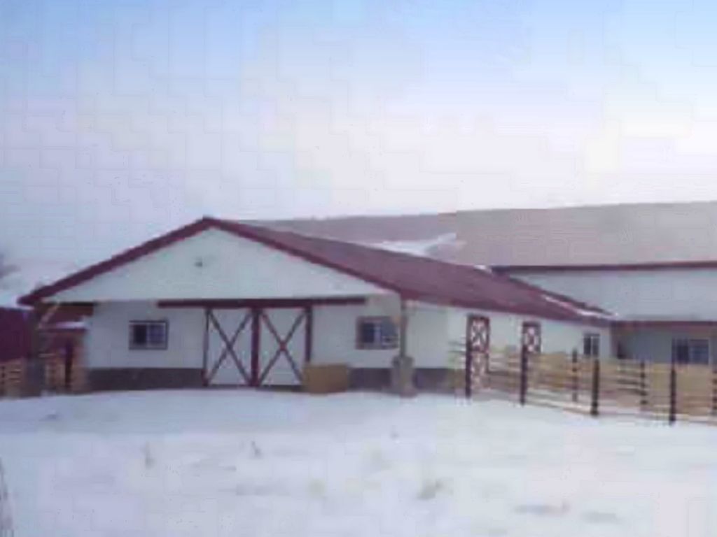 The gable end of a stable attached to a riding arena. Both have a distinctive red roof.
