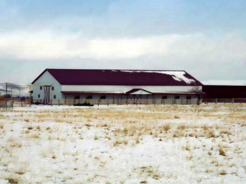 A red steel roof and white steel siding cover a traditional looking riding arena.