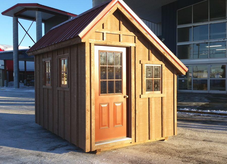Rustic board and batten wood siding with rust-red steel roofing and entry door on an alpine pitched roof cabin style shed.