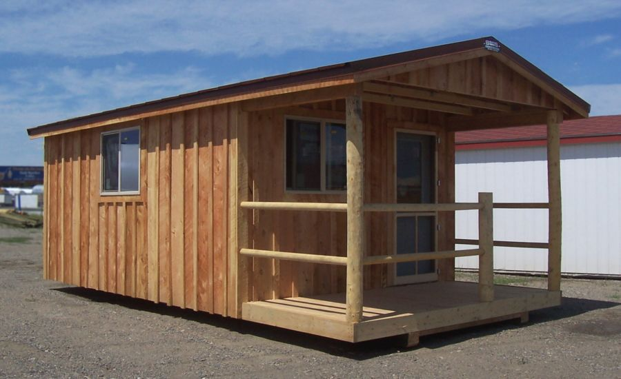 Cabin style shed that has a front porch with rustic wooden posts and railing to complement the board and batten siding.