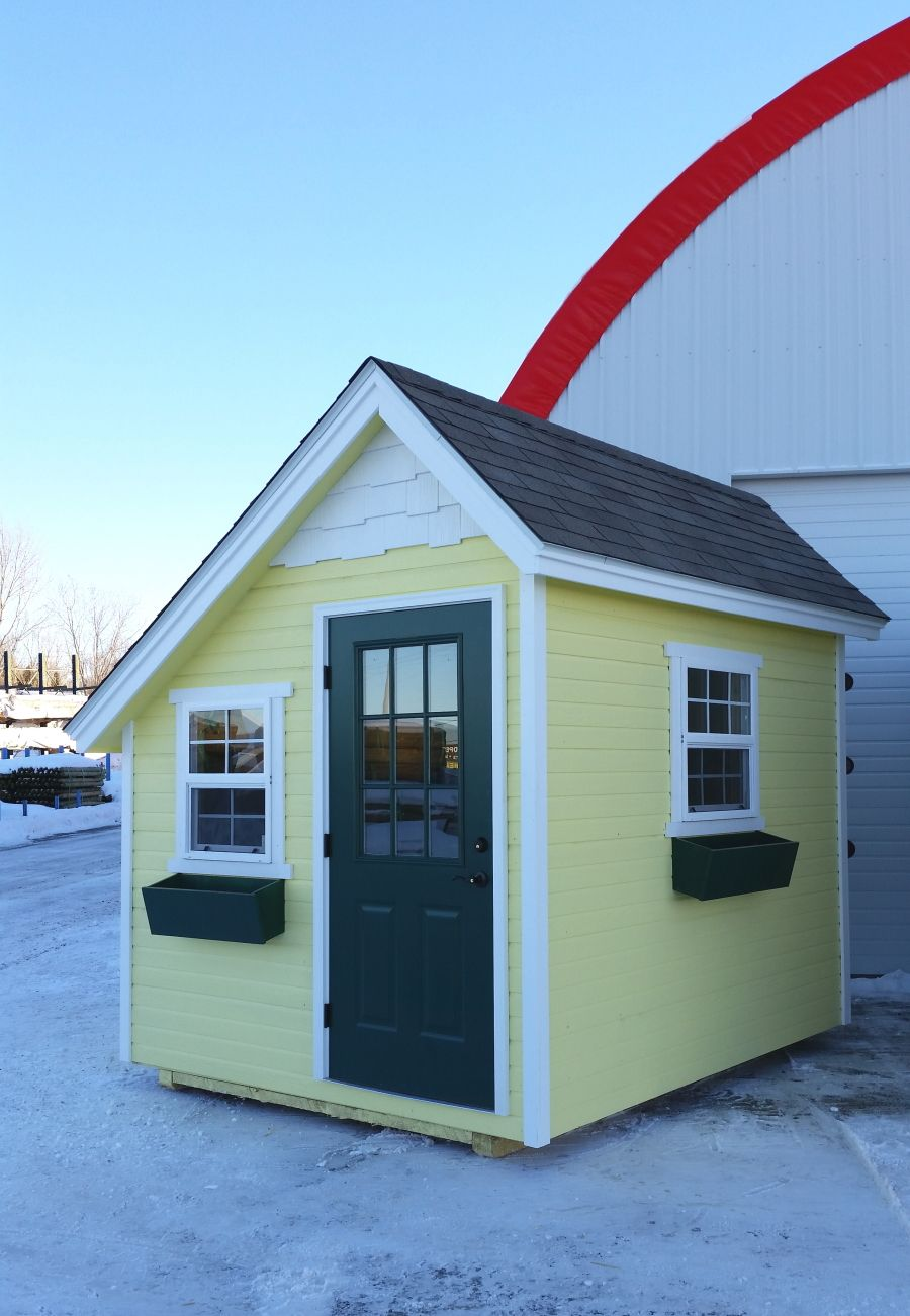 Sunshine yellow siding, white trim, and green painted window boxes and entry door on a she-shed with an alpine pitched roof.