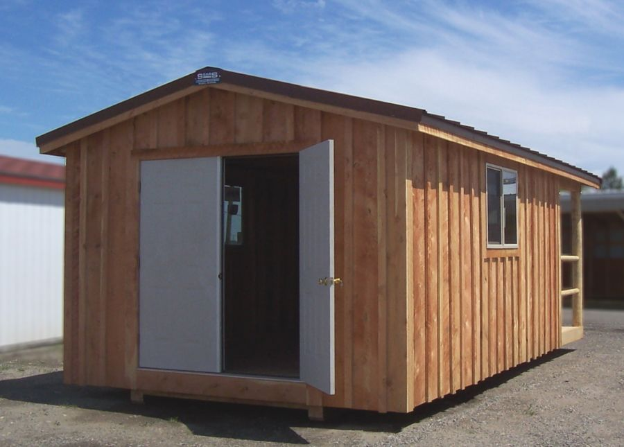 Back of a cabin style shed that has french entry door installed. Board and batten wood siding with a brown steel roof.