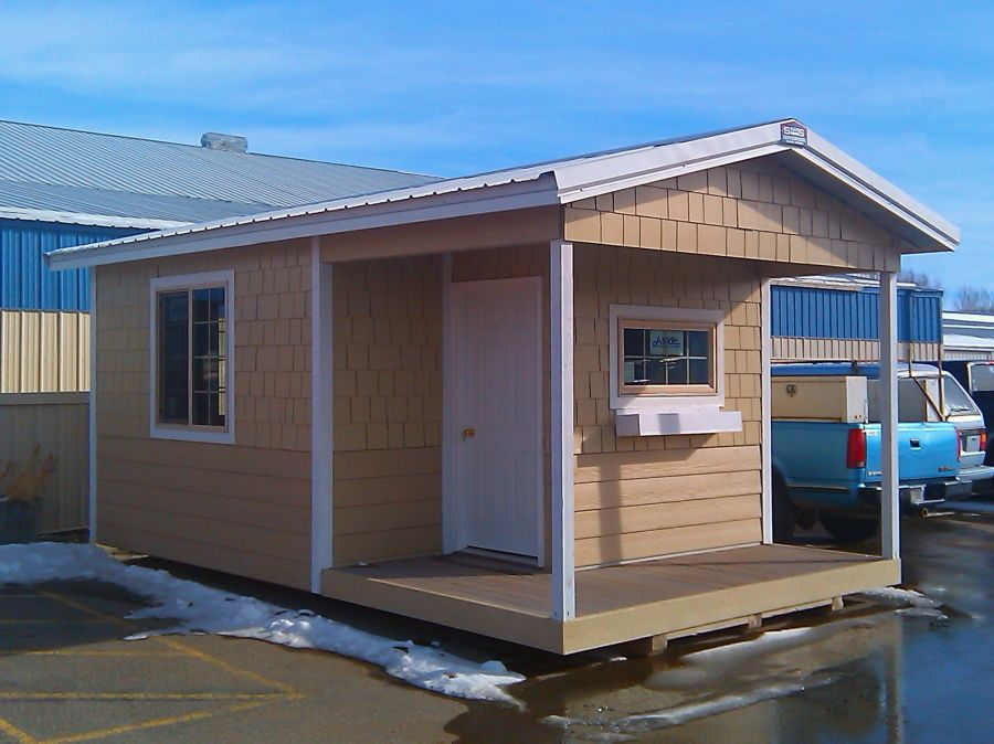 Gable-roofed shed with white steel roof and custom trim. Cabin style with small front porch.