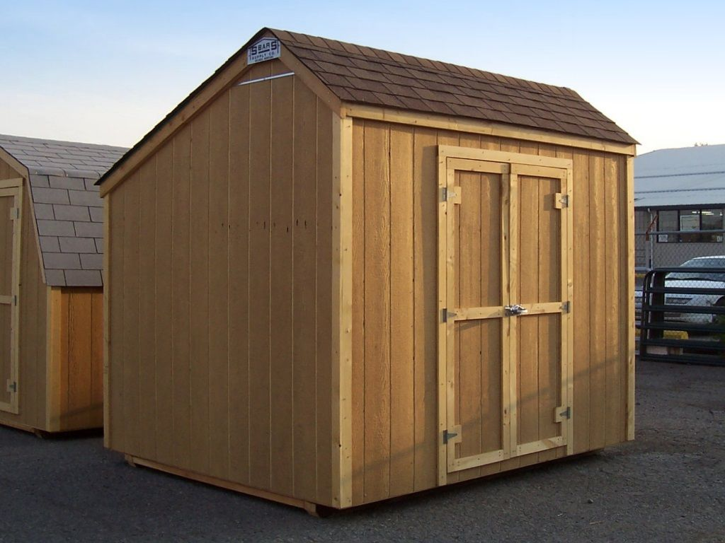 Shed with an off-center roof peak and no eaves. It has brown shingles and wooden T1-11 siding.