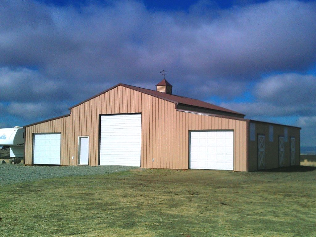 Monitor style shop building with three overhead doors and a cupola on the roof peak.
