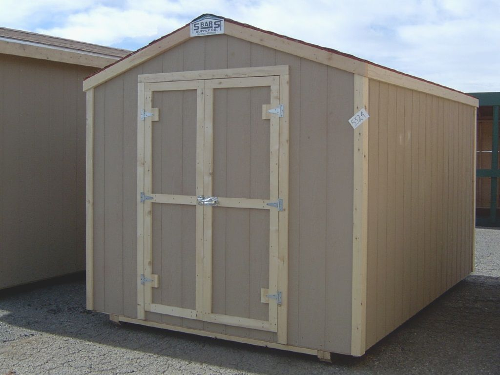 A small gable-roofed shed with no overhang and shed style doors on the end. It has tan shingles and wood trim.