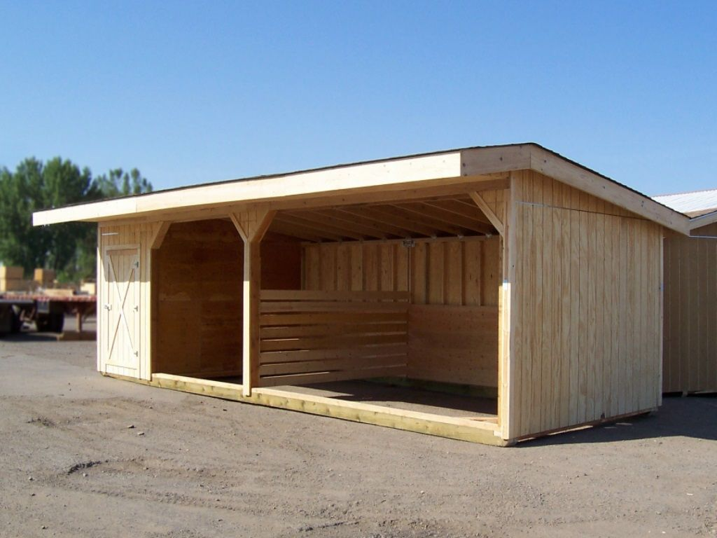 Wood-sided livestock shelter with two bays separated with a divider. A tack room is on one end.