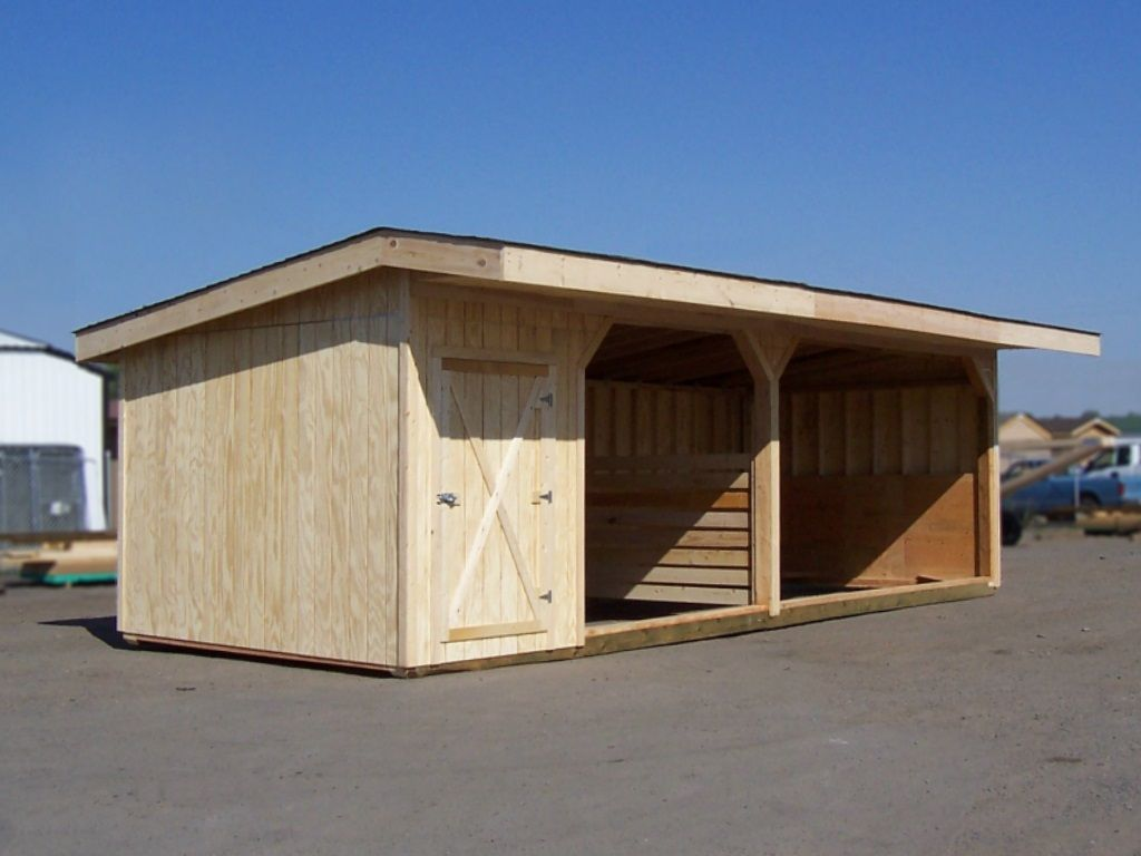 Wood sided livestock shelter with two bays separated with a divider. A tack room is on one end.