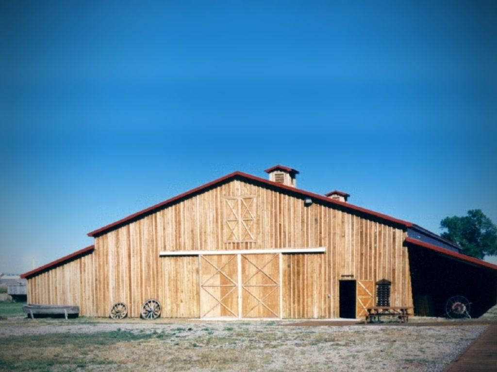 Custom wood siding on a monitor roof building that has a sliding barn door at the end.