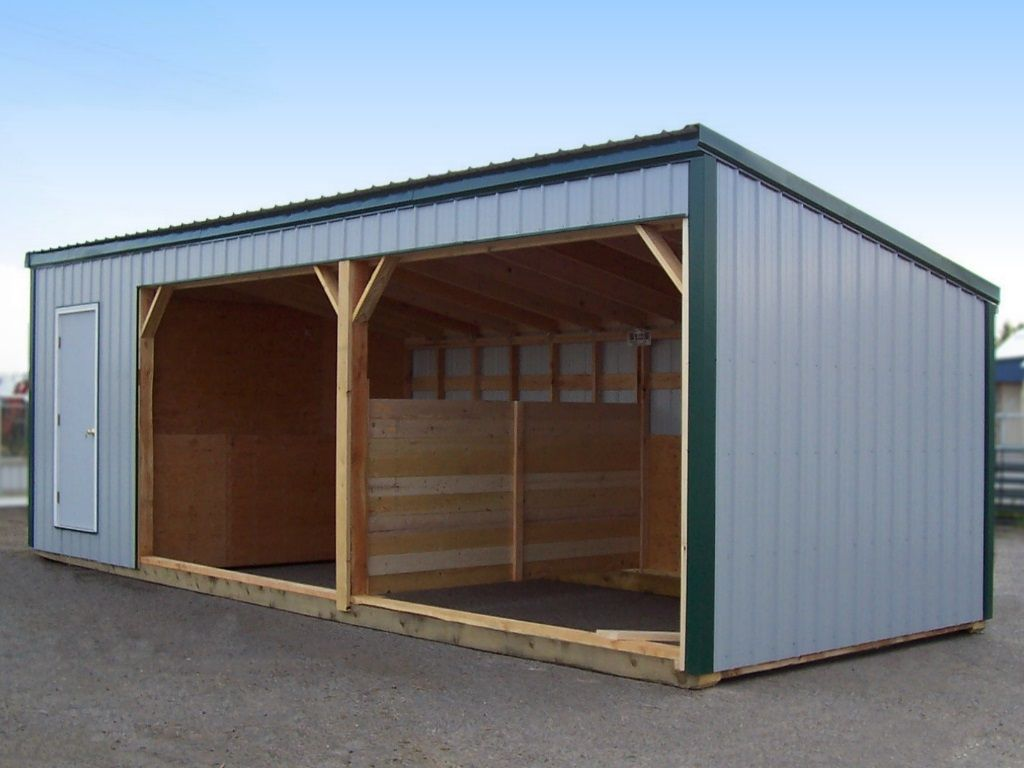 Two-bay livestock shelter with a stall divider and a tack room, all clad in white steel with forest green roofing and trim.