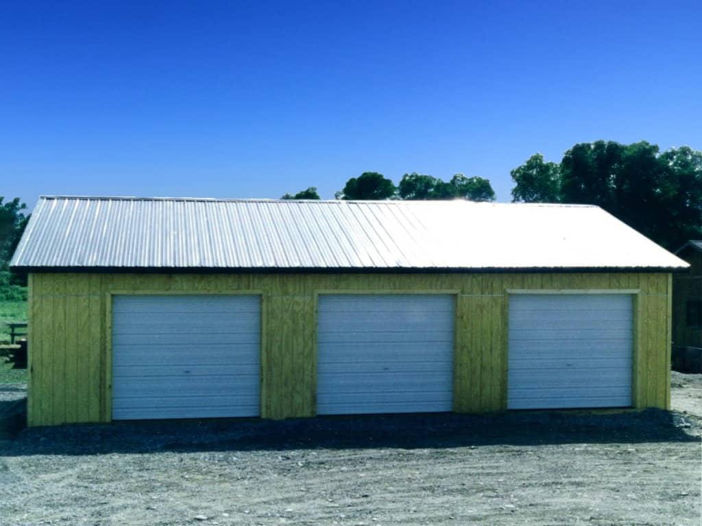 Three car garage with steel roof and custom wood siding.