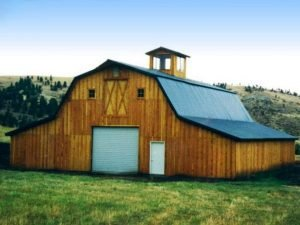 Wooden barn with overhead door and a cupola.