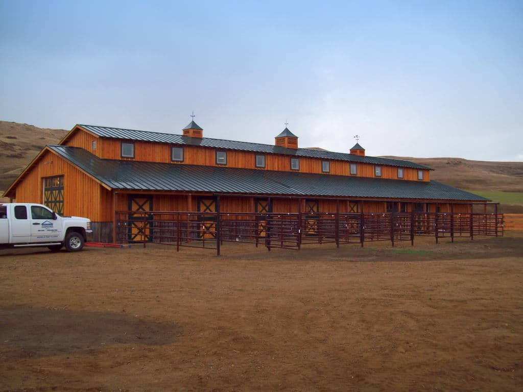 Wooden horse barn with monitor-style roof and cupolas.