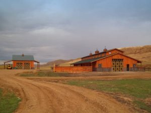 End view of wooden barn and matching outbuilding.