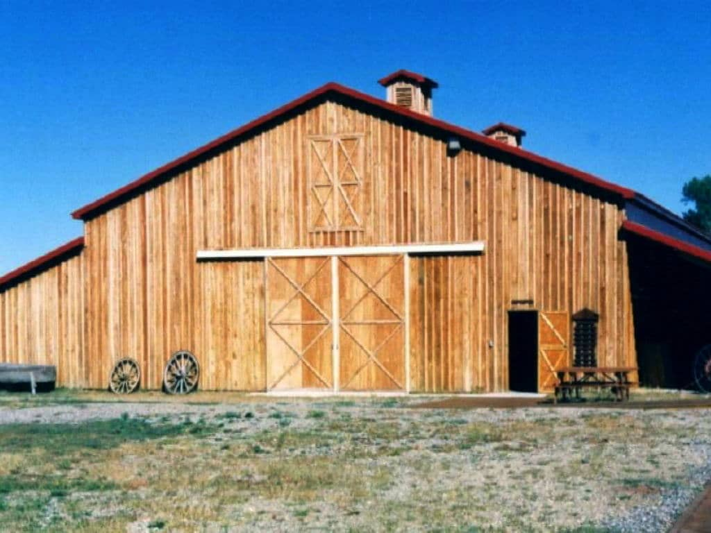 Front of wooden barn with sliding doors.