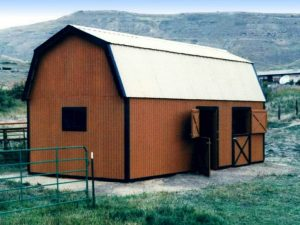 Small wooden barn with gambrel style roof.