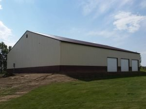 Exterior of a commercial pole building with three overhead doors and steel wainscot.