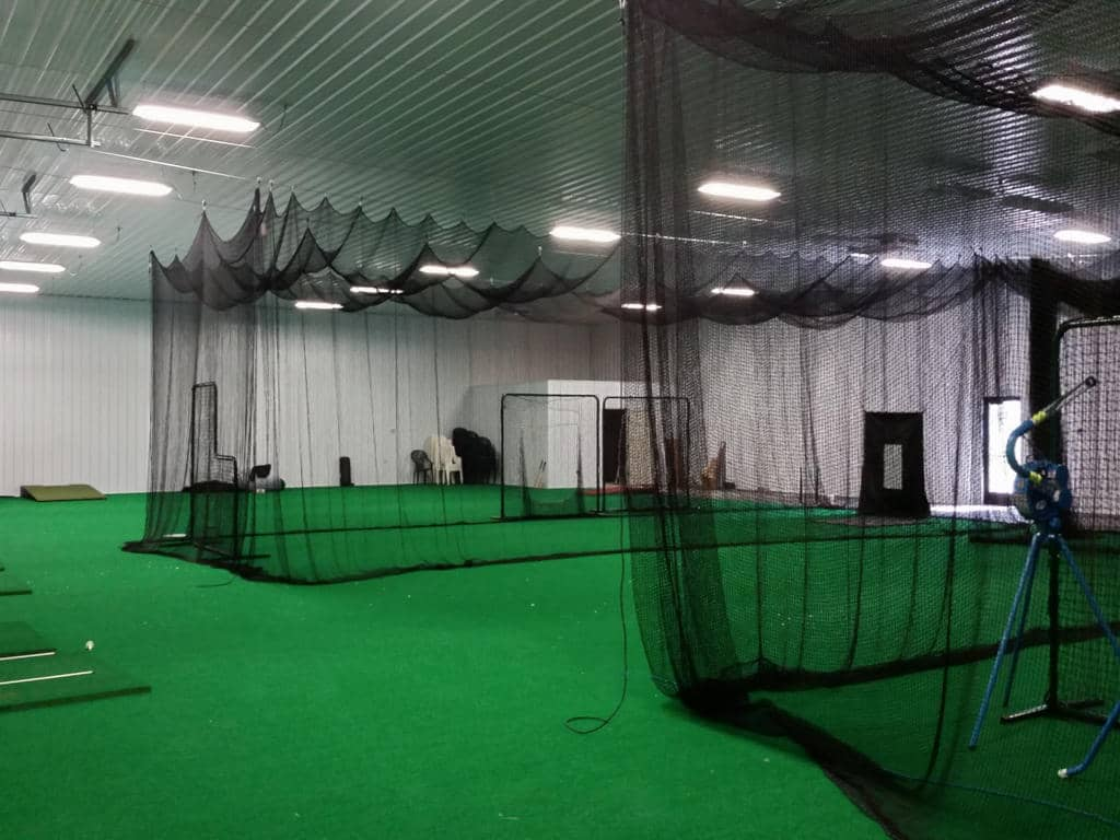 View of netting enclosed driving ranges inside a commercial pole building.