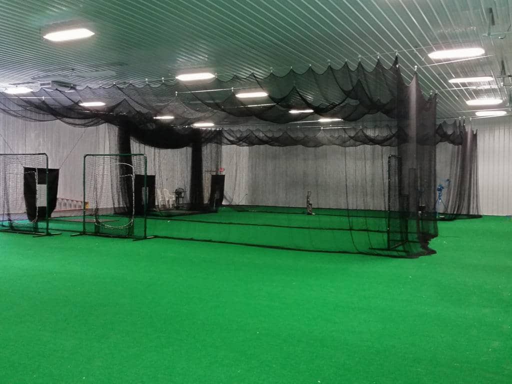 Green astroturf covers the floor of a commercial pole building.