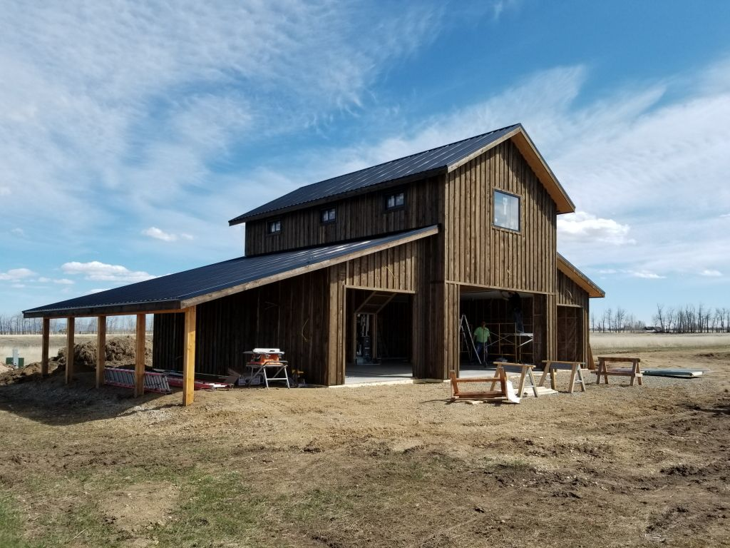 Pole building with monitor style roof and custom board and batten wood siding.