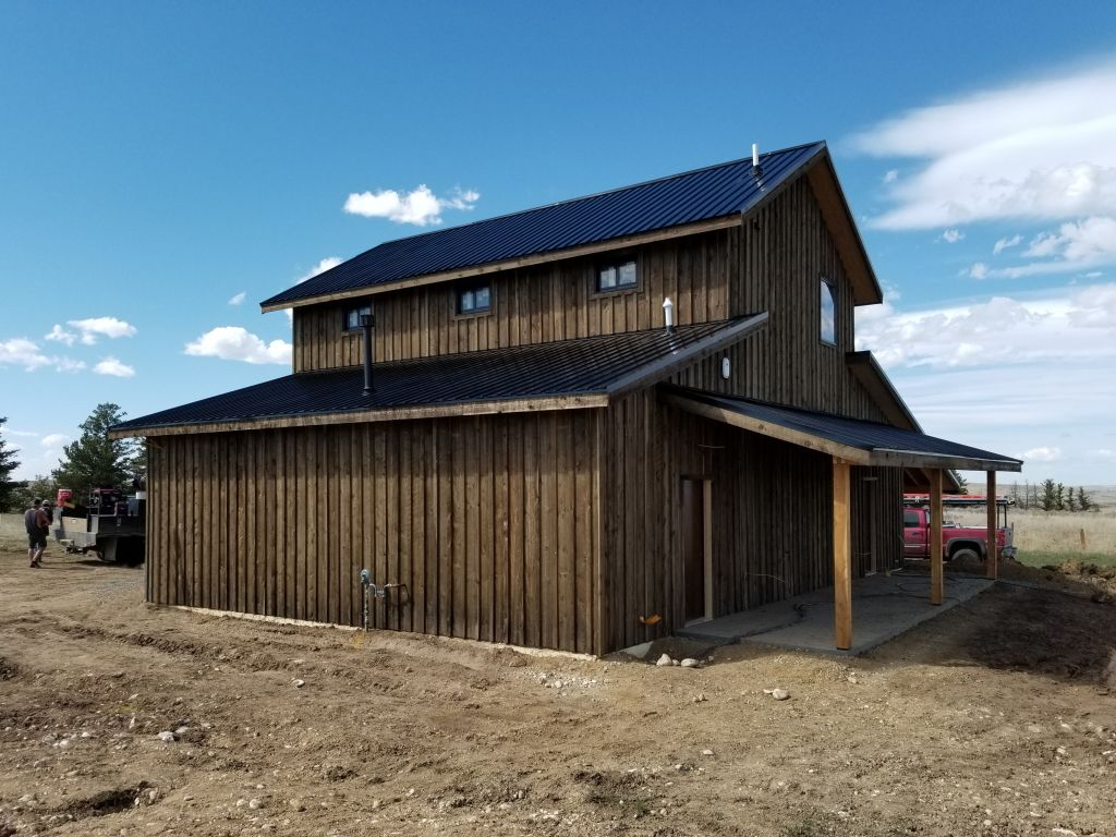 Rear view of a pole building with a monitor roof and custom board and batten wood siding.
