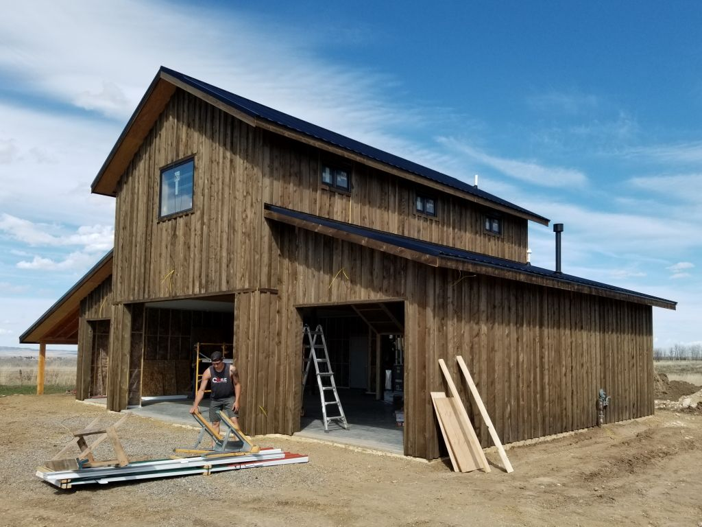End and side view of pole building with monitor roof and custom board and batten wood siding.