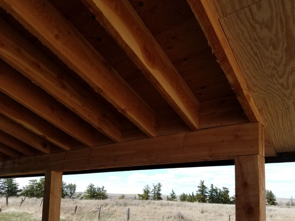 Details of wooden posts, beam, and rafters of a lean-to that is attached to a pole building.
