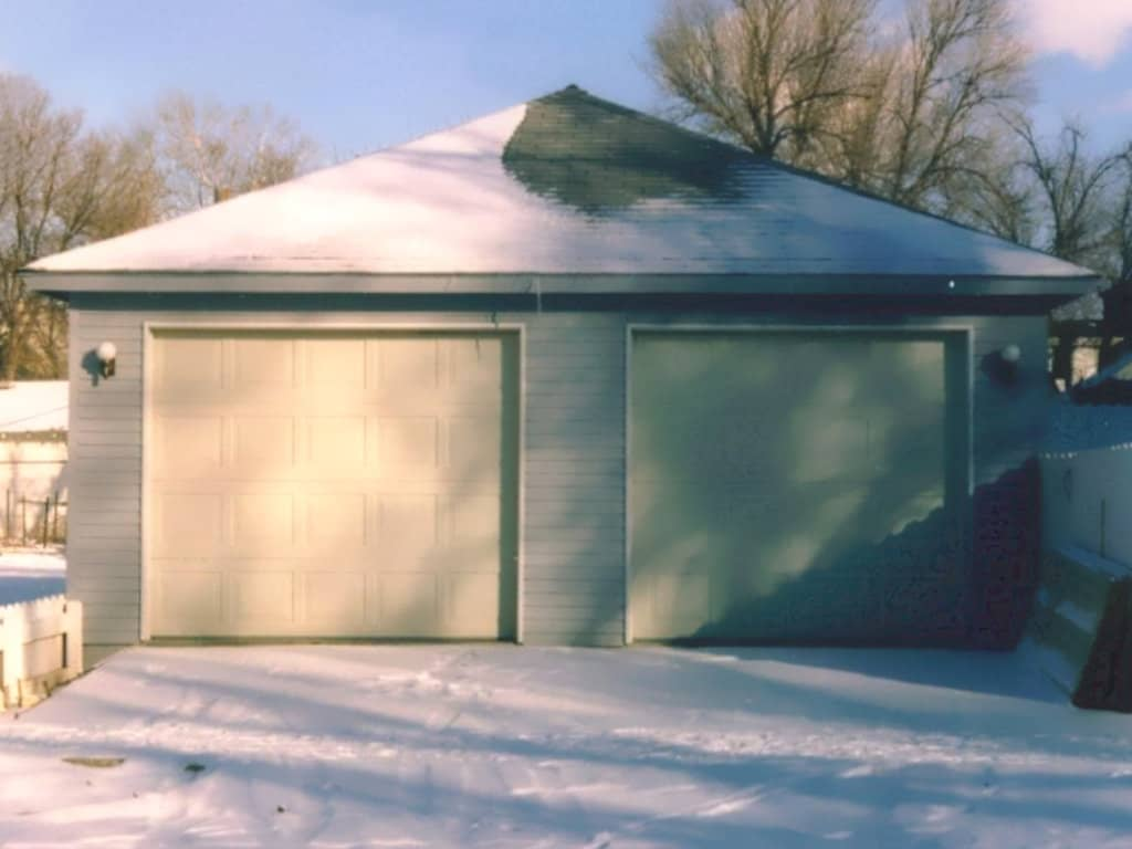 Two car garage with exterior lights and a hipped roof.