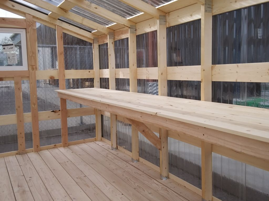 Shelving along the interior of a greenhouse made by S-Bar-S.