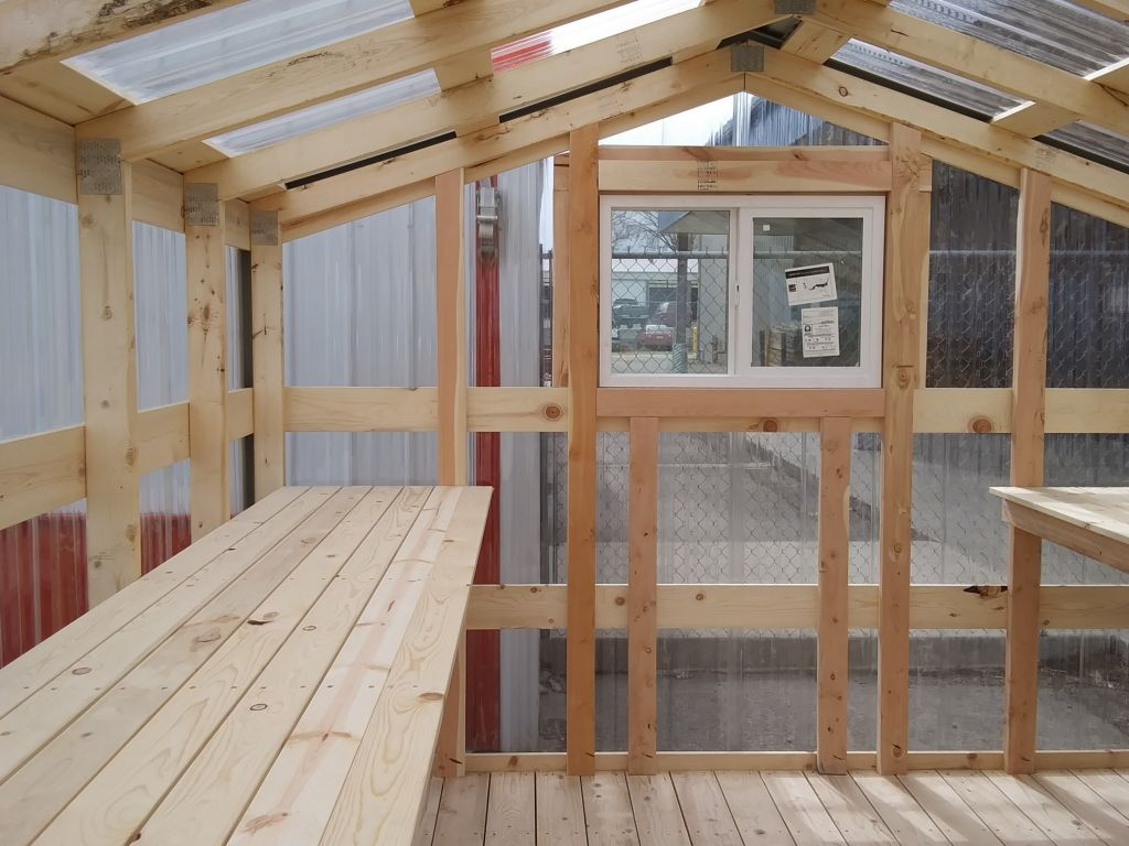 Clear polycarbonate panels make up the roof and siding of a greenhouse from S-Bar-S.