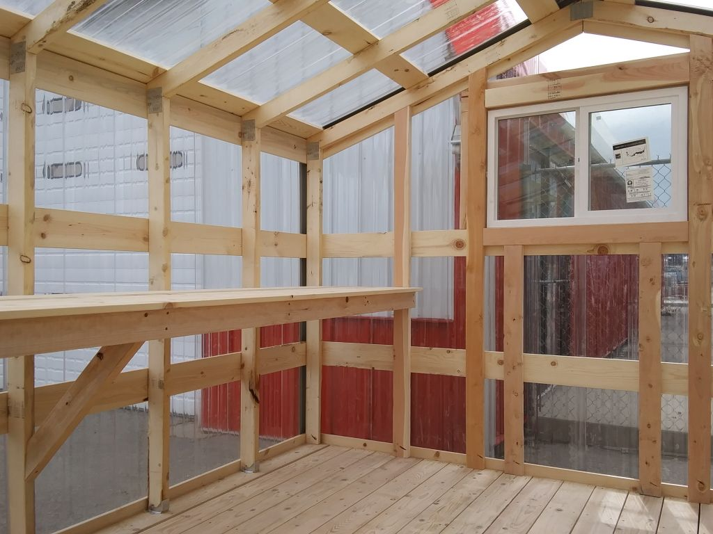 Greenhouse interior with rear window and clear polycarbonate siding.