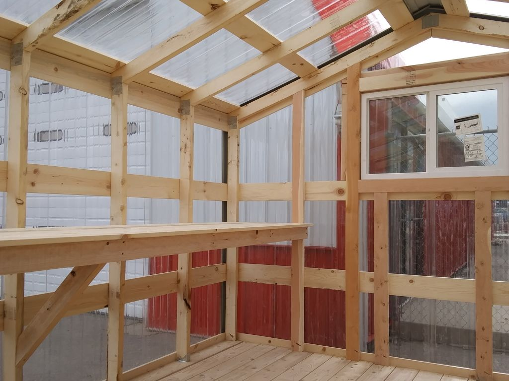 Greenhouse interior with shelves on the side and clear polycarbonate siding