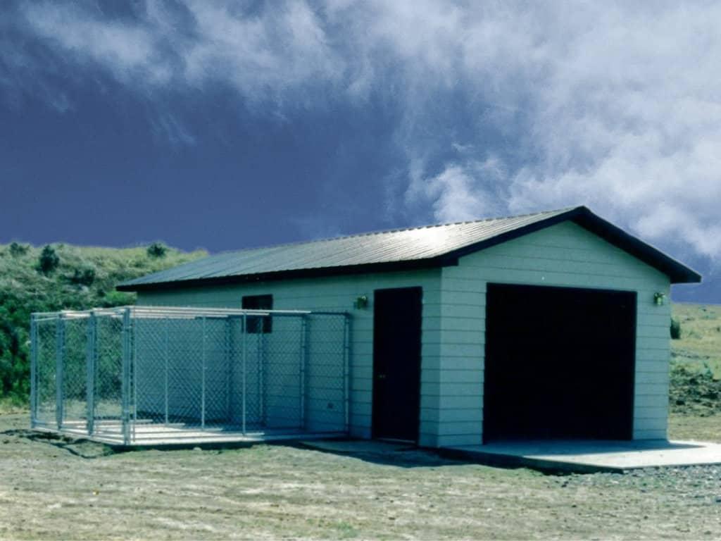 Unattached garage with window and walk door. Garage has attached dog kennels.