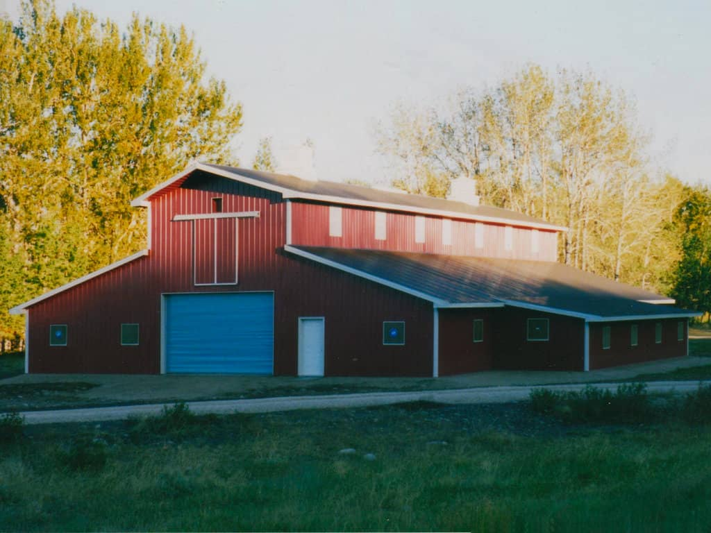 Red, steel-clad pole barn with monitor roof.