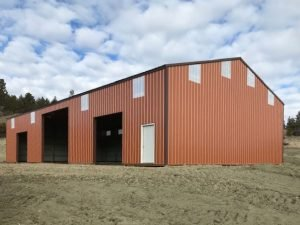 Sid view of the front and a gable end of a steel-sided pole barn built by S-Bar-S.