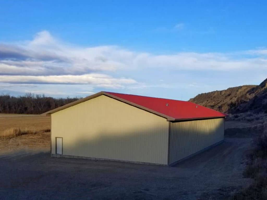 Red-roofed pole barn with walk door on the gable end.
