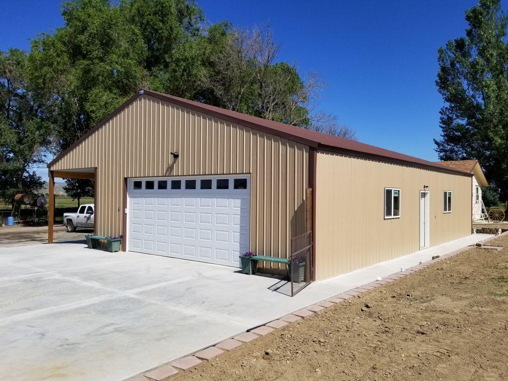 Metal-sided pole barn garage with windows, overhead door, walk door and lean-to shown.