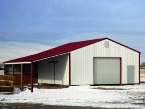 A lean-to sits on one side of a gable-roofed pole barn that has red metal roofing and trim with white metal siding.