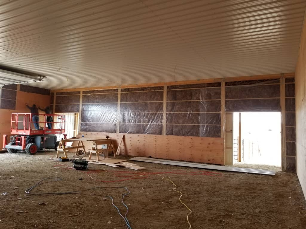 Turned girt frame with insulation & vapor barrier being covered with plywood.