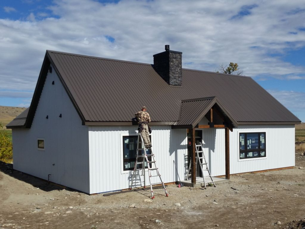 Man on ladder finishes installing metal roof trim on a post-frame home with a portico entry.