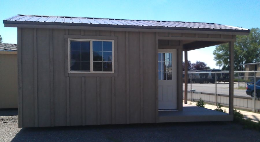 Gable-roofed shed with front porch and sided in board and batten wood.