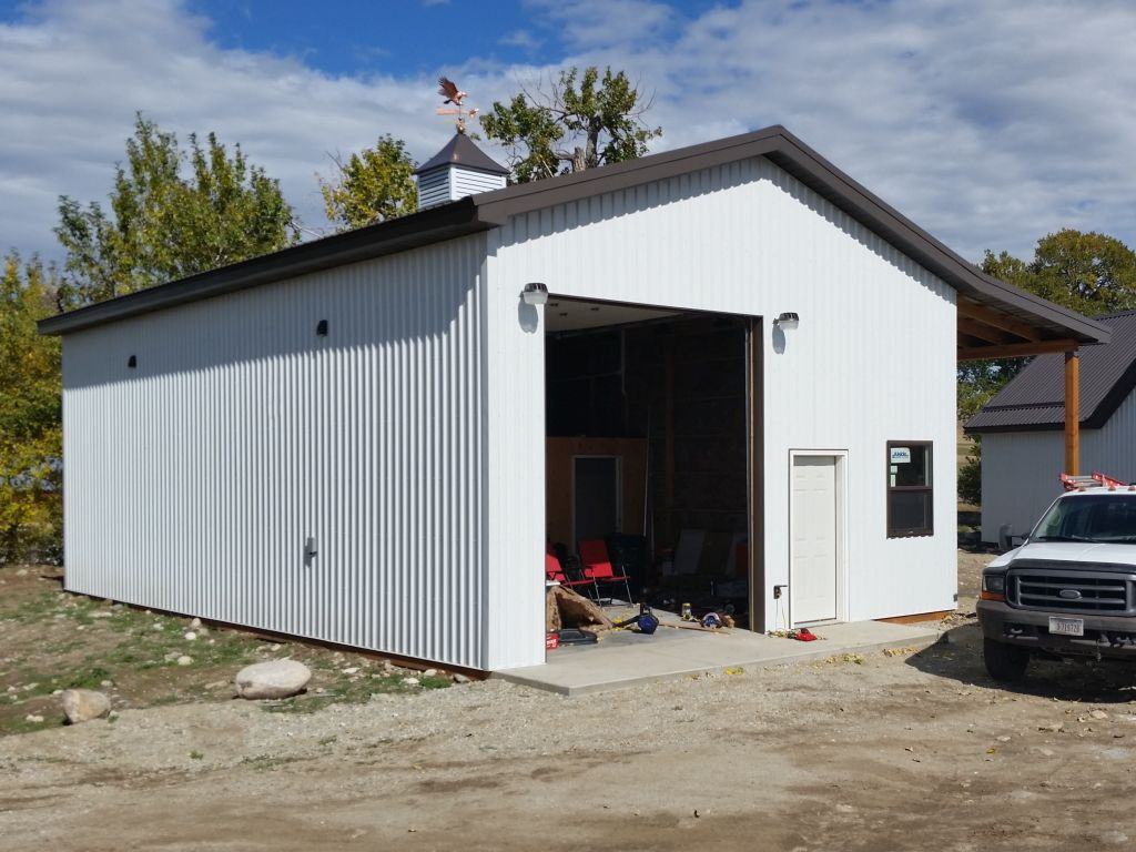 White steel sided garage with a cupola and weathervane on the gable roof.
