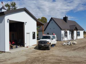 Post-frame home and garage with S-Bar-S crew finishing construction.