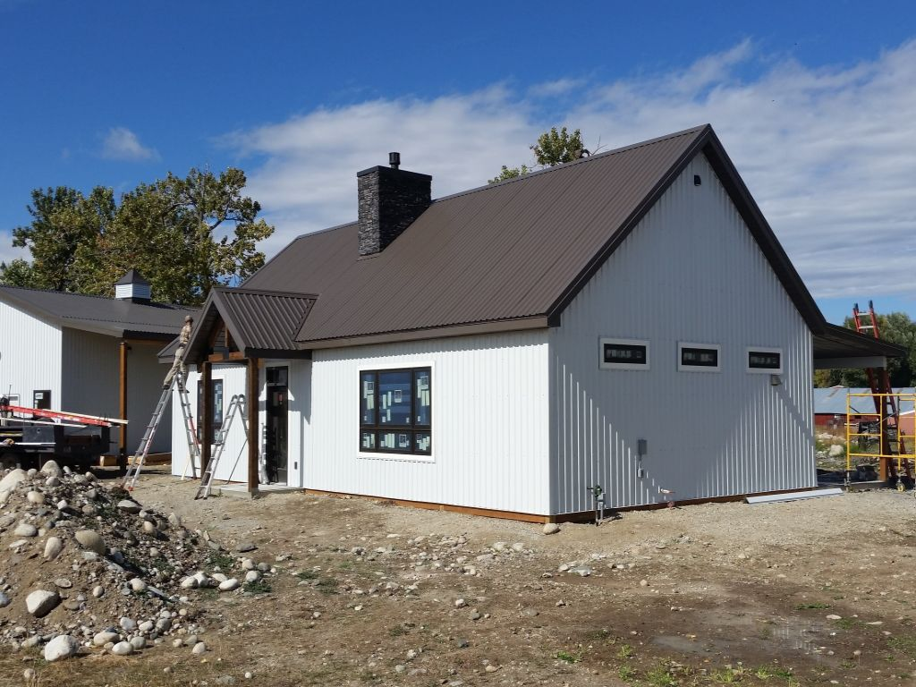 White steel siding and a brown steel roof on a post-frame home that is being constructed by S-Bar-S.