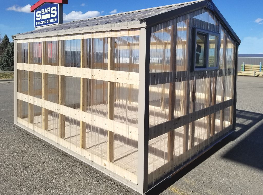 Clear polycarbonate panels show the wooden interior frame of a greenhouse.