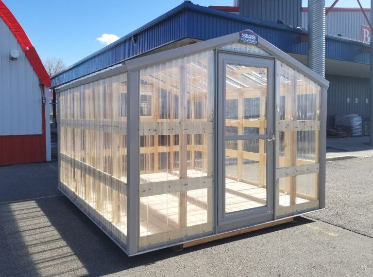 Storm door entrance of a greenhouse with a gable roof.