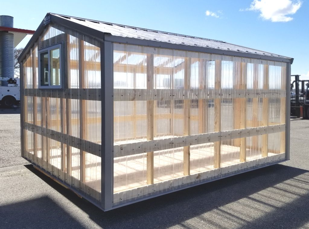 Exterior of a greenhouse that has clear polycarbonate panels and steel trim.