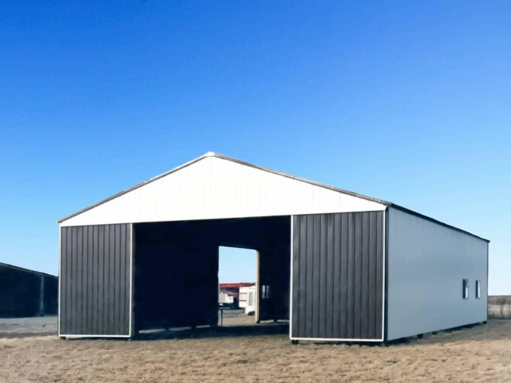 Steel-sided pole barn with sliding barn doors on gable end.