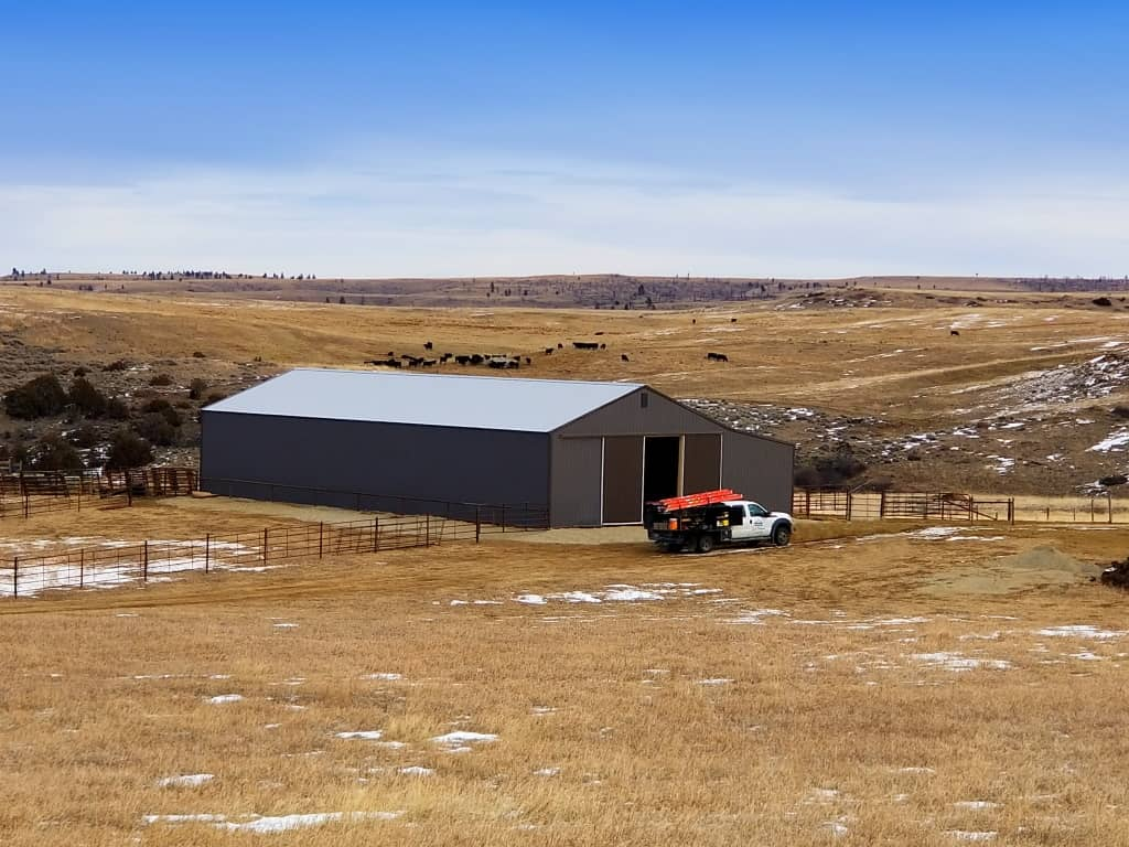 Gray steel sided pole building for livestock and storage.
