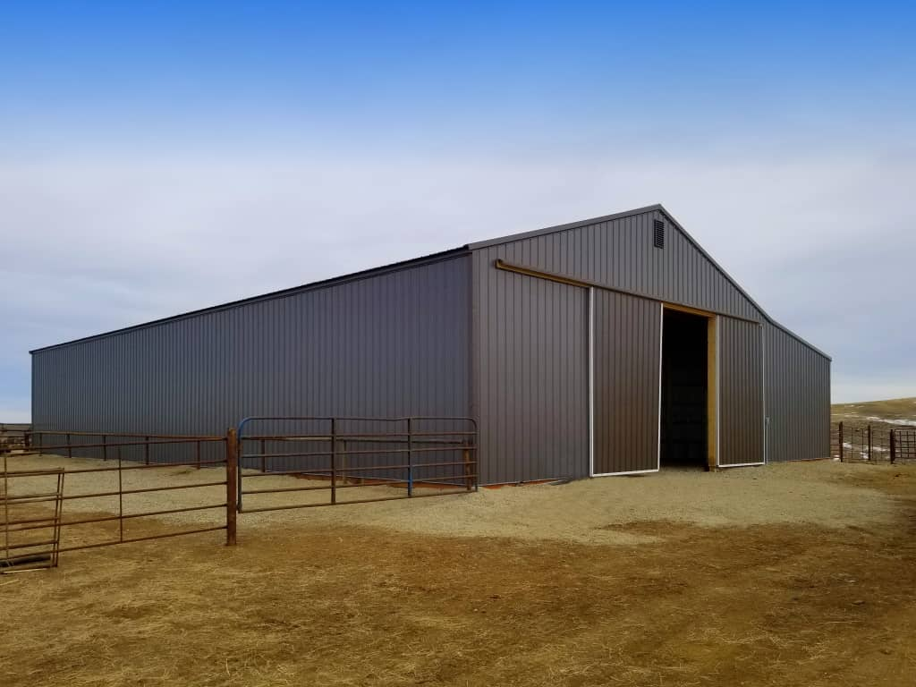 Gray steel sided building with a sliding barn door on the gable end.